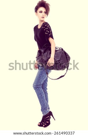 Full length beautiful young woman with handbag posing in studio - stock photo