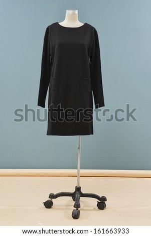 full length black sundress on a dummy isolated on a blue background - stock photo