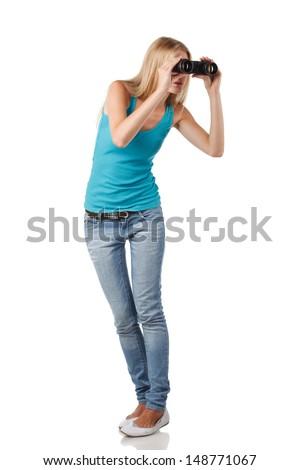 Full length blond woman looking through binoculars sideways - stock photo