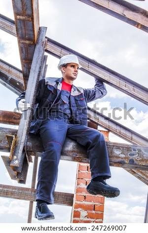 Full length body portrait of worker on a steel beam raises his hands sitting on rusty structure metal beam - roof frame, Under construction on blue summer sky background with clouds - stock photo