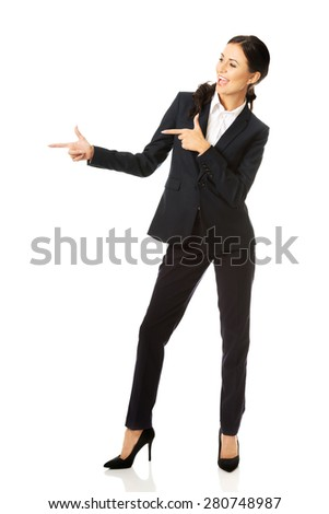 Full length businesswoman pointing to the right. - stock photo