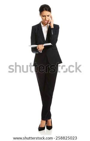 Full length businesswoman reading her notes. - stock photo