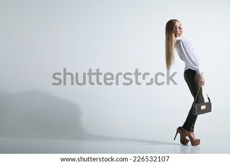 Full length casual young fashionable woman with a bag in light background - stock photo