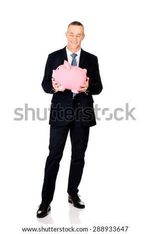Full length cheerful businessman holding piggybank. - stock photo