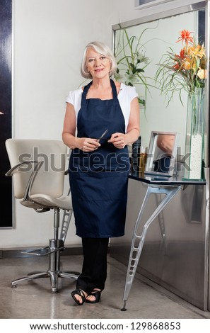 Full length environmental portrait of senior female hairdresser standing at salon - stock photo