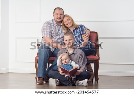 Full length family portrait with parents and two children sitting on sofa and reading a book, studio shot - stock photo