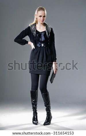 full-length fashion model in autumn/winter clothes holding handbag posing  - stock photo