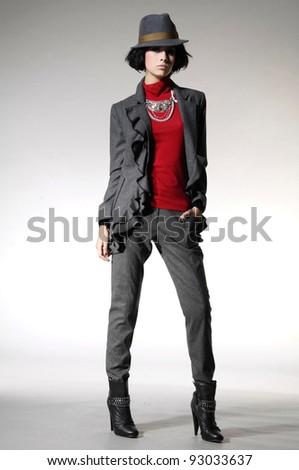 full-length fashion model in fashion dress posing on light background - stock photo