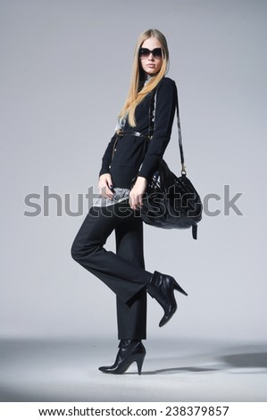 full-length fashion model in fashion dress with handbag posing on gray background - stock photo