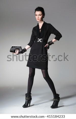 full-length fashion model in gloves holding little purse posing-light background    - stock photo