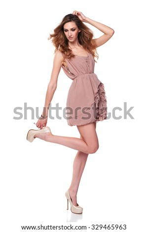 Full length fashion model in gorgeous pale rose color dress posing over white background, motion shot - stock photo