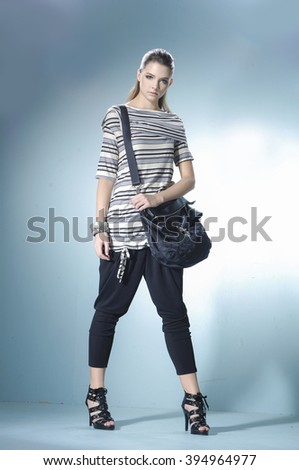 Full length fashion model with bag posing in light background - stock photo