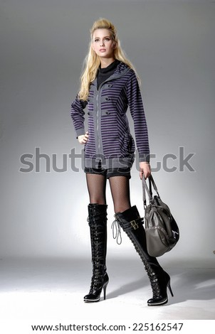 full-length fashion or casual woman holding bag posing studio - stock photo
