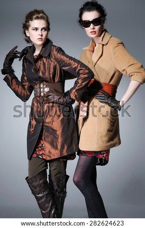 full-length fashion two model in coat clothes posing on light background  - stock photo
