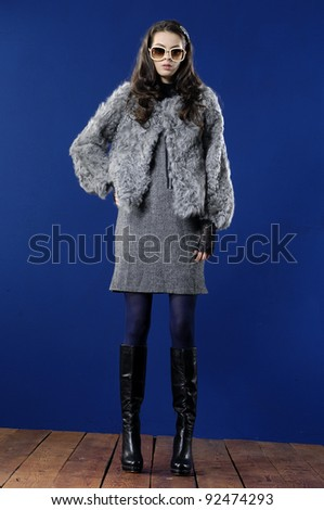 Full length fashion woman in fur coat posing wooden floor - stock photo