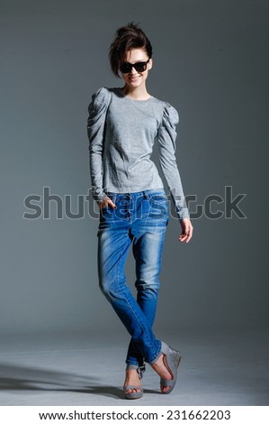 Full length fashion woman studio in jeans on gray background - stock photo