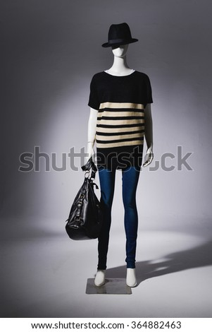 full-length female in hat with bag on mannequin in light background - stock photo