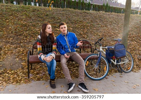 Full Length Front View of Young Couple in Conversation Sitting Together on Bench Next to Bicycle in Urban Park on Chilly Autumn Day - stock photo