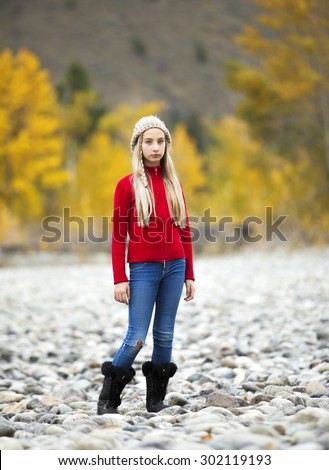 Full length, front view photo of pretty, young girl standing in a nature setting with autumn colors in background - stock photo