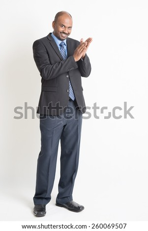 Full length happy Indian businessman in formal suit clapping hands and looking at camera, on plain background. - stock photo