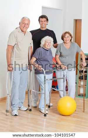 Full length happy portrait of disabled senior people with trainer - stock photo