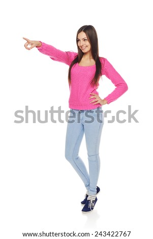 Full length happy young female in blue jeans and pink sweater pointing at blank copy space over white background - stock photo