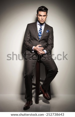 Full length image of a elegant business man holding his hands while sitting on a stool, looking at the camera and thinking. - stock photo