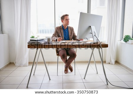 Full length image of a young businessman sitting at his desk  working on his computer in a contemporary work space for one - stock photo