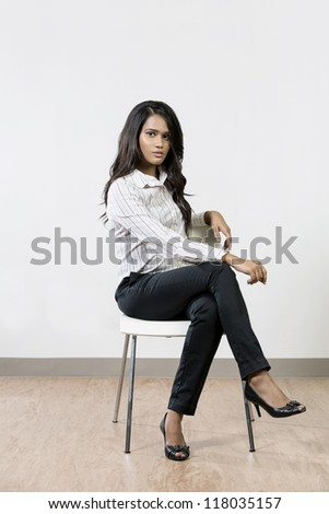 Full length image of a young Indian business woman sitting on chair. - stock photo