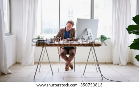 Full length image of a young male entrepreneur sitting at his desk in a contemporary work space for one person and writing in his journal - stock photo