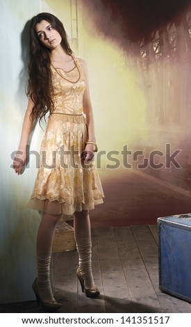 Full length image of an attractive young girl posing on wooden floor - stock photo