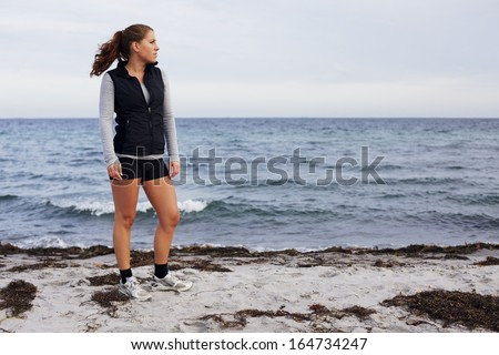 Full length image of beautiful young woman standing on beach looking away. Healthy female athlete relaxing after a run on sea shore. Caucasian young woman on beach looking at copyspace - stock photo