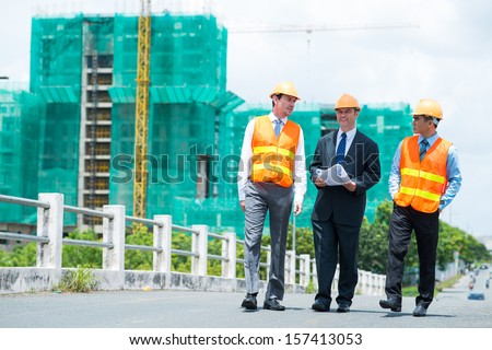 Full-length image of constructor engineers walking and discussing the project outdoors - stock photo