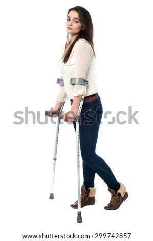Full length image of teen walking with crutches - stock photo