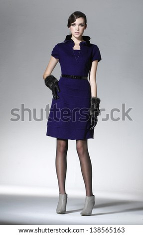 Full length image of young fashion model in gloves posing - stock photo