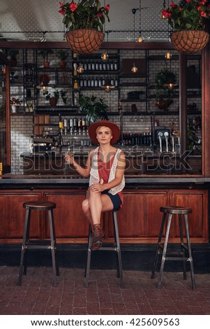 Full length indoor shot of beautiful young woman sitting at a cafe with a drink. Caucasian female relaxing at a coffee shop counter. - stock photo