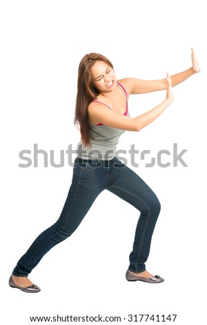 Full length isolated on white background of Asian woman in casual clothes with extended arms open palms, struggling, forcing, leaning, pushing against imaginary product placement object. Copy Space - stock photo