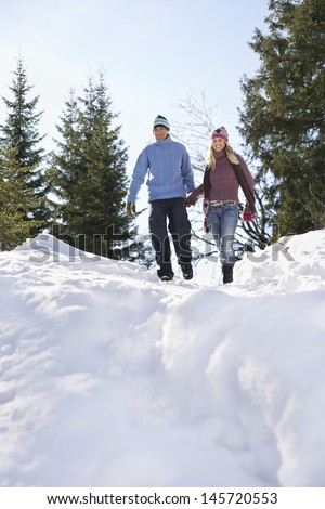 Full length low angle view of a couple descending snow covered hill - stock photo