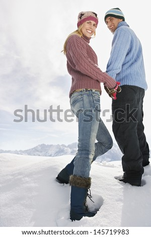 Full length low angle view of a couple holding hands on snow covered hill - stock photo