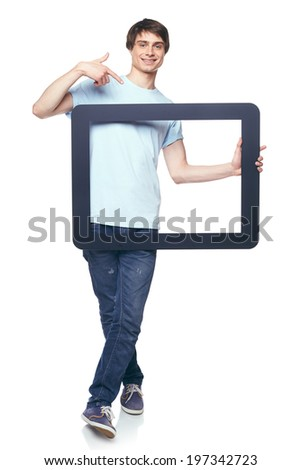 Full length man holding tablet frame and pointing at it, over white background - stock photo
