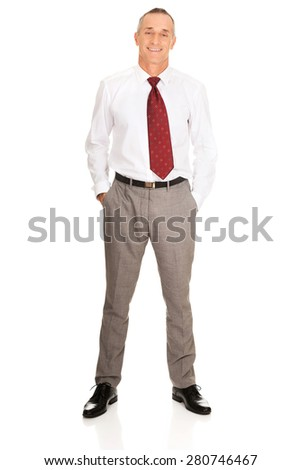 Full length mature businessman with hands in pockets. - stock photo
