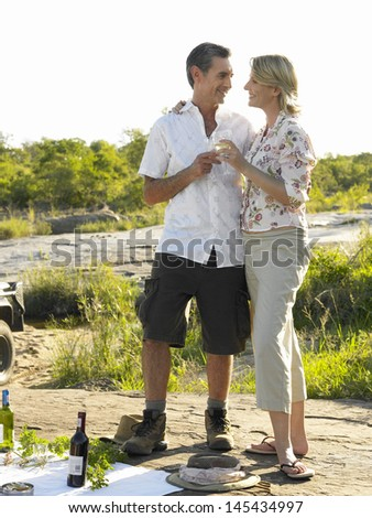 Full length of a couple toasting wine on open landscape - stock photo