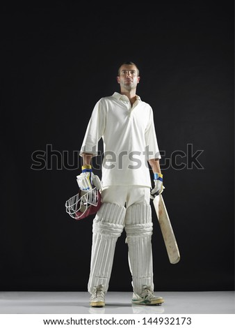 Full length of a cricket player holding bat and helmet against black background - stock photo