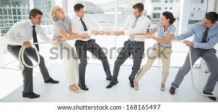 Full length of a group of business people playing tug of war in office - stock photo