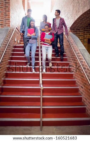 Full length of a group of young college students walking down stairs in the college - stock photo