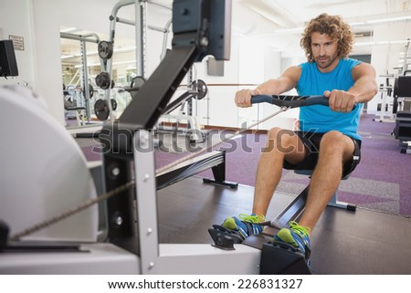 Full length of a handsome young man using resistance band in gym - stock photo
