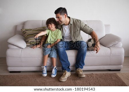 Full length of a happy father and son with football watching tv in the living room at home - stock photo