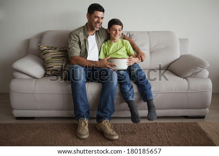 Full length of a happy father and son with popcorn bowl watching tv in the living room at home - stock photo
