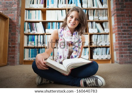 Full length of a happy female student sitting against bookshelf with a book on the library floor - stock photo