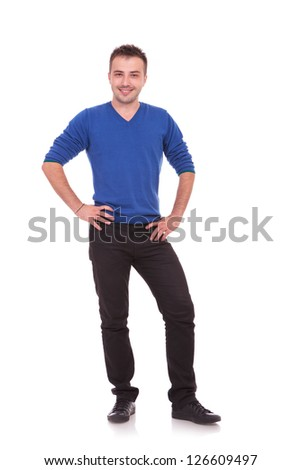 Full length of a happy young man with hands on hips against white background - stock photo